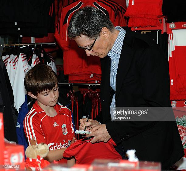 In this handout image supplied by Liverpool Football Club, John W Henry of NESV signs an autograph for a young fan in the Liverpool F.C. Shop at...