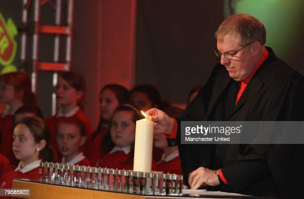 In this handout image supplied by Manchester United Rev John Boyers of Manchester United lights a candle during the memorial service to mark the 50th...