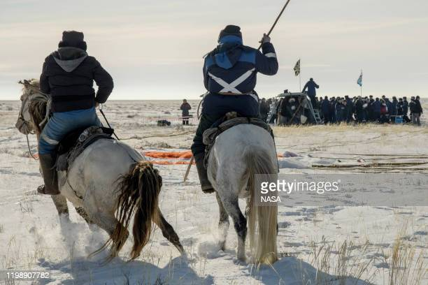 In this handout image supplied by NASA, Two locals on horseback arrive at the Soyuz MS-13 spacecraft shortly after it landed in a remote area near...