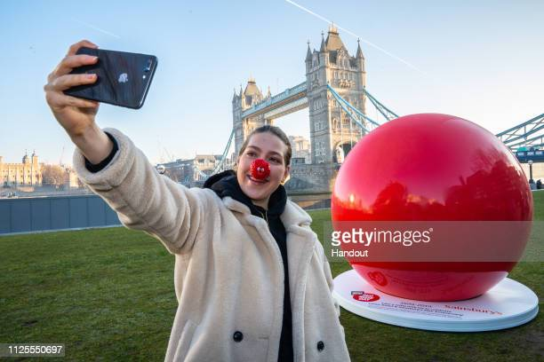 In this handout image supplied by Sainsburys/ Comic Relief a giant red nose has popped up in Potter's Field Park in front of Tower Bridge as...