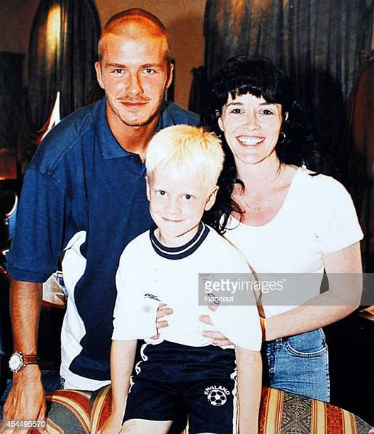 In this handout image supplied by Sainsbury's David Beckham Jonnie Peacock aged 7 and his mother Linda Green pose for a photograph on their first...