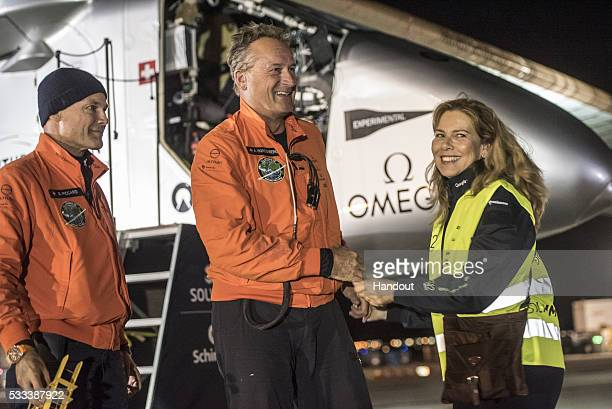 In this handout image supplied by SI2 Swiss adventurer Andre Borschberg is welcomed by his wife Yasemin and alternate pilot Bertrand Piccard after...