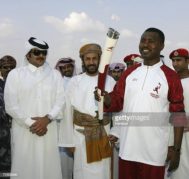 In this handout image supplied by the Doha Asian Games Organising Committee , The Torch relay Ambassador, H.E.Sheikh Joaan Bin Hamad Al Thani and...