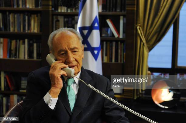 In this handout image supplied by the Israeli Government Press Office , President Shimon Peres speaks on the phone to the Israeli aid team currently...