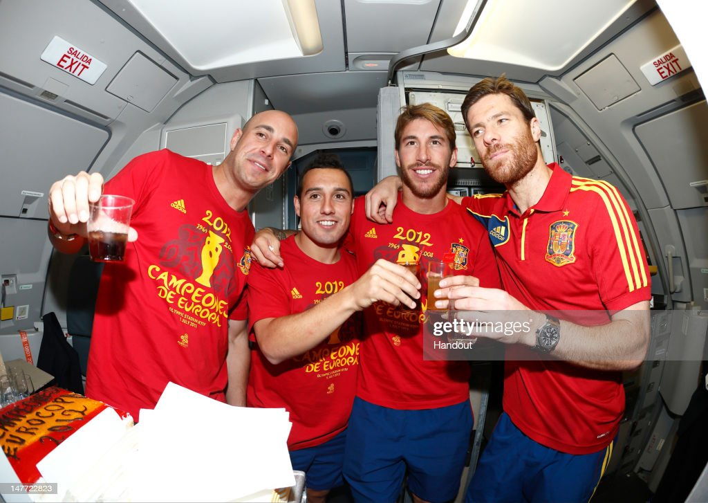 In this handout image supplied by the Royal Spanish Football Federation, (L-R) Pepe Reina, Santi Cazorla, Sergio Ramos and Xabi Alonso of Spain celebrate following their team's victory in the UEFA EURO 2012 final match against Italy onboard the Spain team's airplane during their flight back to Madrid on July 2, 2012 in flight.