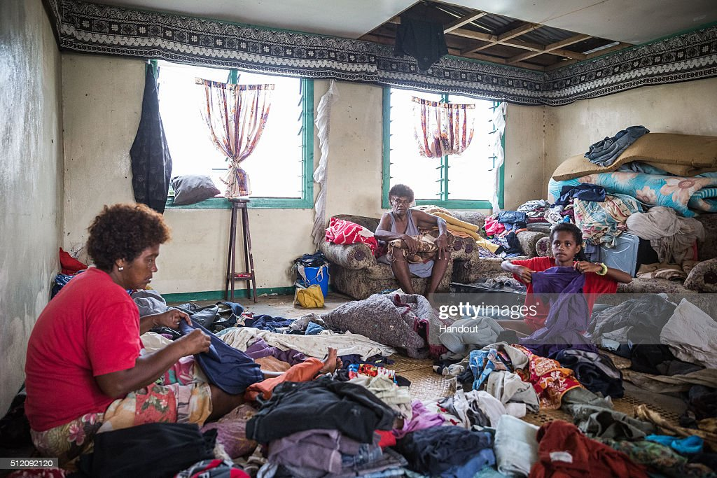 In this handout image supplied by the UNICEF, 10-year-old Lusiana (R) is helping her grandmother (C) and aunt (L) sort through and fold clothes for her family in Rakiraki district in Ra province in Fiji on February 24, 2016 in Fiji. Category 5 Tropical Cyclone Winston made landfall in Fiji on Saturday 20 February, continuing its path of destruction into Sunday 21 February. A state of natural disaster and a nationwide curfew had been declared by the Government of Fiji earlier in the evening. The Fijian Government has declared a state of natural disaster for the next 30 days and has initiated the clean-up process by clearing the huge amounts of debris scattered everywhere.