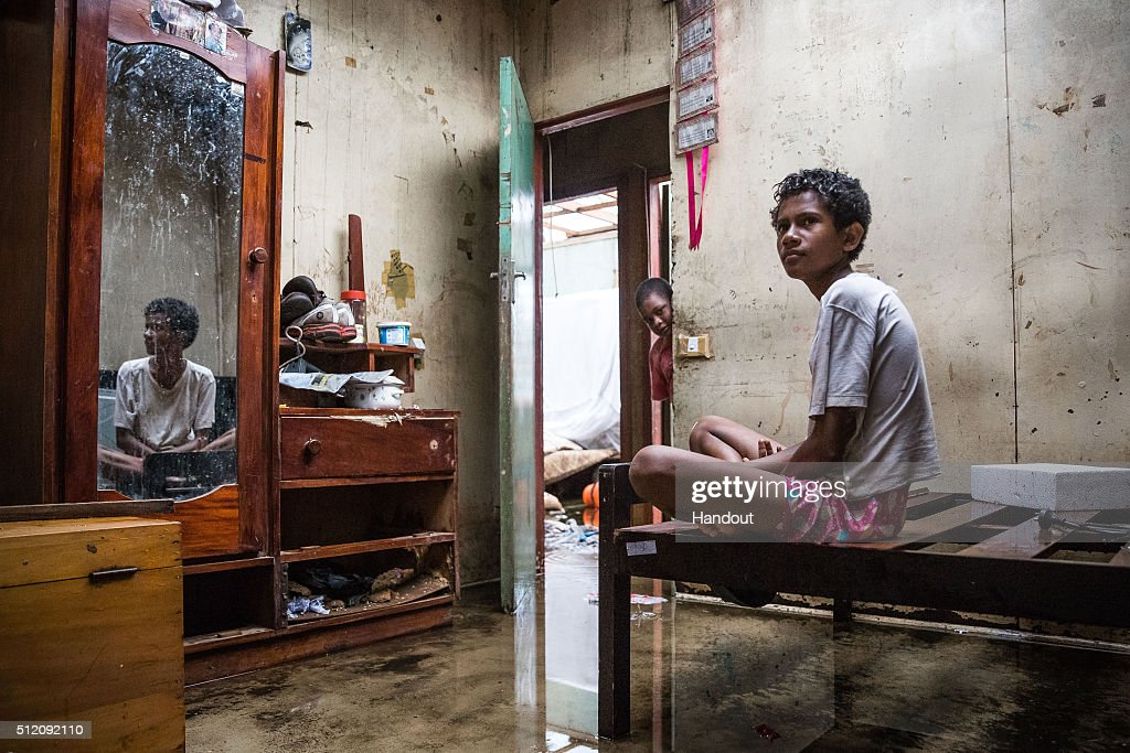 In this handout image supplied by the UNICEF, Makereta Nasiki, 13, sits in her room, showing damage caused by Tropical Cyclone Winston in the town of Ba on Viti Levu Island on February 24, 2016 in Fiji. Category 5 Tropical Cyclone Winston made landfall in Fiji on Saturday 20 February, continuing its path of destruction into Sunday 21 February. A state of natural disaster and a nationwide curfew had been declared by the Government of Fiji earlier in the evening. The Fijian Government has declared a state of natural disaster for the next 30 days and has initiated the clean-up process by clearing the huge amounts of debris scattered everywhere.