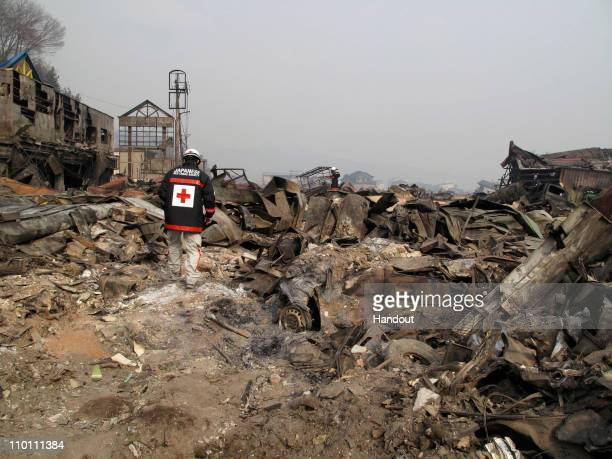 In this handout images provided by the International Federation of Red Cross Japan A member of the Japanese Red Cross team walks through what is left...