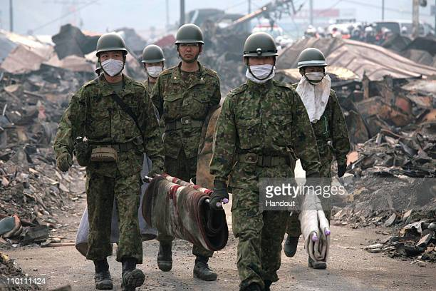 In this handout images provided by the International Federation of Red Cross Japan, Japanese self-defense forces search for missing people, after an...