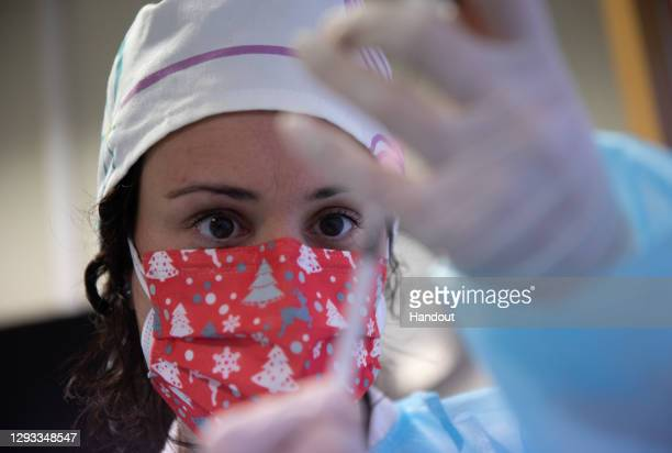 In this handout photo, A health professional prepares the first dose of the Pfizer/BioNTech Covid-19 vaccine in the Somontano nursing home on...