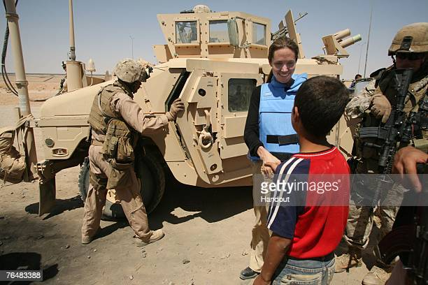In this handout photo Angelina Jolie talks to an Iraq child August 28, 2007 at the Al Waleed refugee camp, Iraq. Jolie, the UNHCR goodwill...
