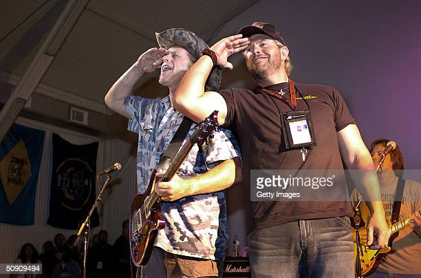In this handout photo, country singer Toby Keith and rock guitarist Ted Nugent salute troops after a United Services Organization performance May 29,...