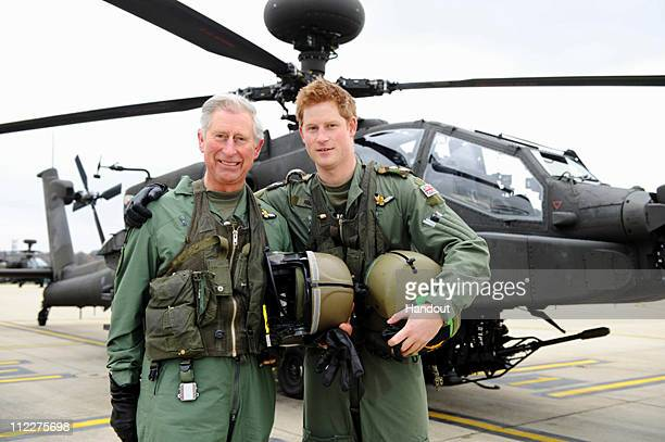 In this handout photo dated March 21 issued by the Ministry of DefencePrince Harry and his father the Prince Charles Prince of Wales stand in front...