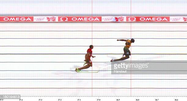 In this handout photo finish image supplied by Omega Usain Bolt of Jamaica crosses the finish line ahead of Ryan Bailey of the United States to win...