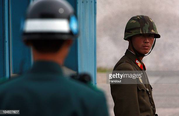 In this handout photo from Chosun Daily News a North Korean Soldier looks at South Korean soldier at the border village of Panmunjom between North...