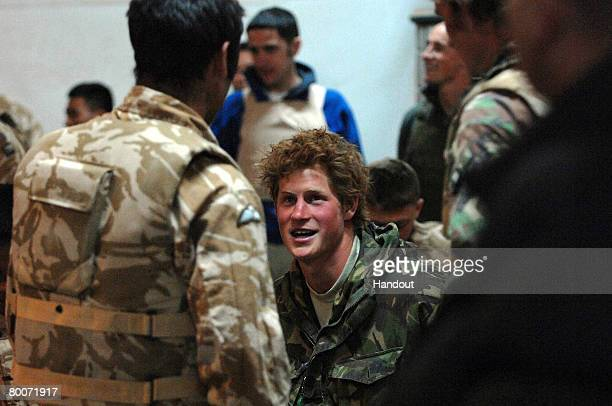 In this handout photo from the British Ministry of Defense Prince Henry of Wales talks with other officers at Kandahar Air field Air terminal...