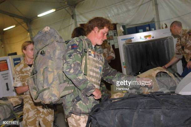 In this handout photo from the British Ministry of Defense Prince Henry of Wales checks in his bags with the RAF Police at Kandahar Air field Air...