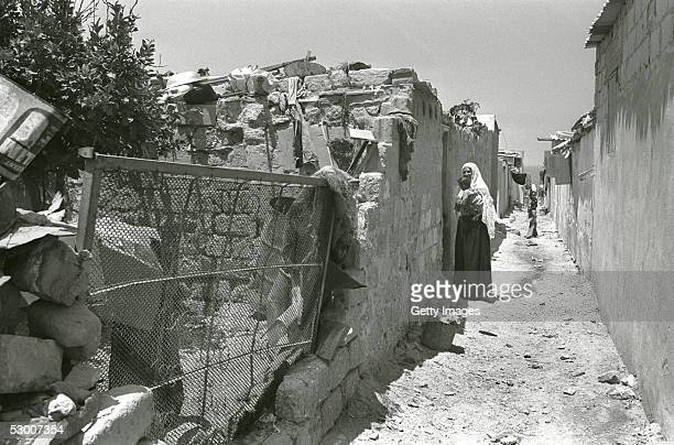 In this handout photo from the GPO A Palestinian refugee carries her child in a narrow street of the Shati refugee camp more than eleven years after...