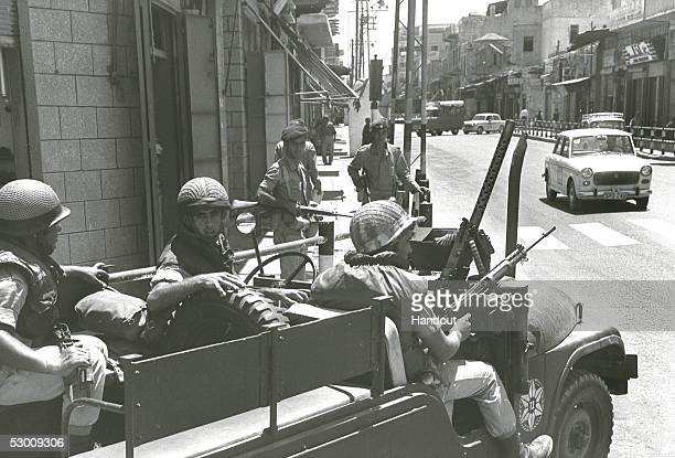 In this handout photo from the GPO an Israeli army patrol passes along the city's main shopping street some four years after the 1967 SixDay War...