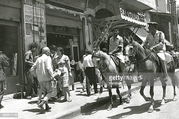 In this handout photo from the GPO Palestinian mounted policemen who answer to the Israeli military government patrol the city's main street almost...
