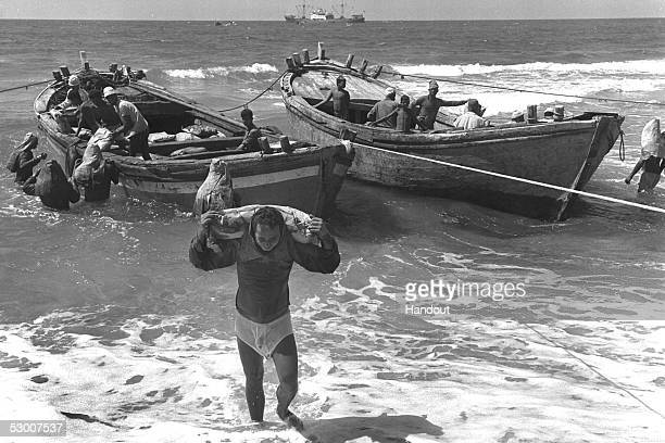 In this handout photo from the GPO Palestinian workers wade through shallow waters as they unload sacks of cement brought by small boats from a...