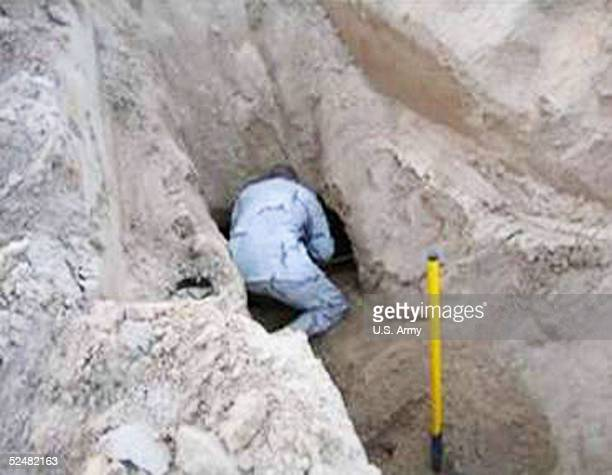 In this handout photo from the US Army released March 26 a soldier is seen inspecting the entrance of a tunnel that was dug leading out of the Camp...