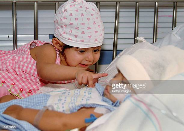 In this handout photo from UCLA Maria de Jesus Quiej Alvarez points at her sleeping sister Maria Teresa at UCLA's Mattel Children's Hospital on June...