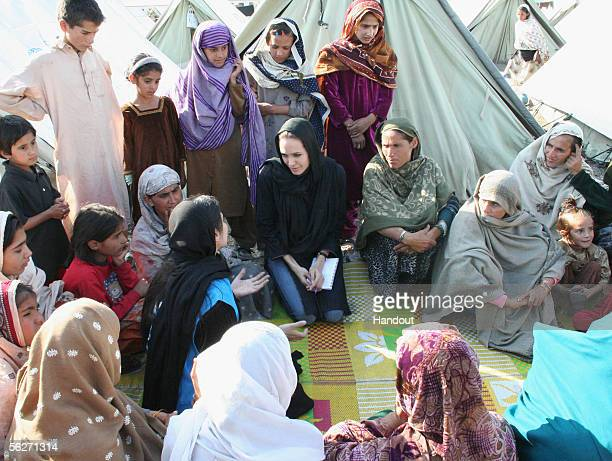 In this handout photo from United Nations Humanitarian Commitee of Refugees Goodwill Ambassador Angelina Jolie talks with women who survived the...