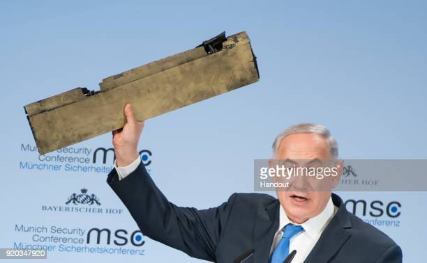 In this handout photo Israeli Prime Minister Benjamin Netanyahu holds up what he claims is a piece of an Iranian drone that was shot down after it...