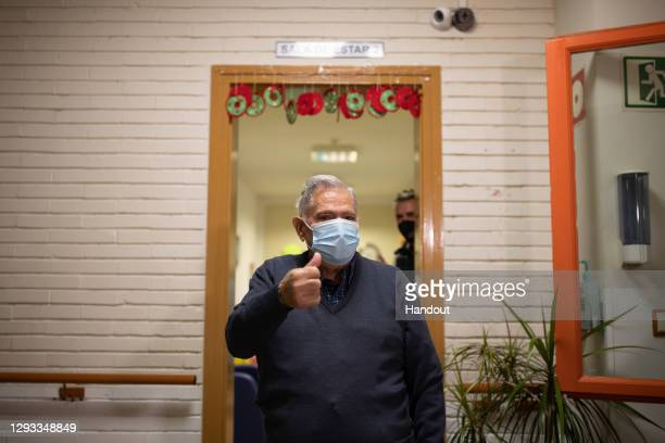 In this handout photo, José Bruballa celebrates after receiving one of the first Pfizer/BioNTech Covid-19 vaccines in Spain at the Somontano nursing...