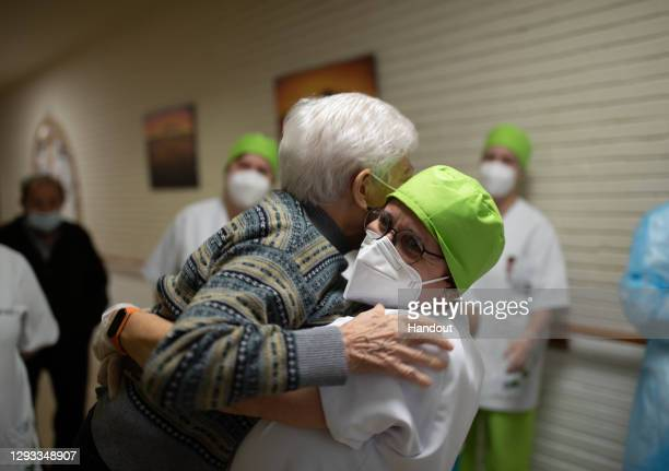 In this handout photo, Lidia Navarro is hugged by a health worker moments before receiving one of the first Pfizer/BioNTech Covid-19 vaccines in...