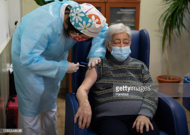 In this handout photo, Lidia Navarro receives one of the first Pfizer/BioNTech Covid-19 vaccines in Spain at the Somontano nursing home on December...