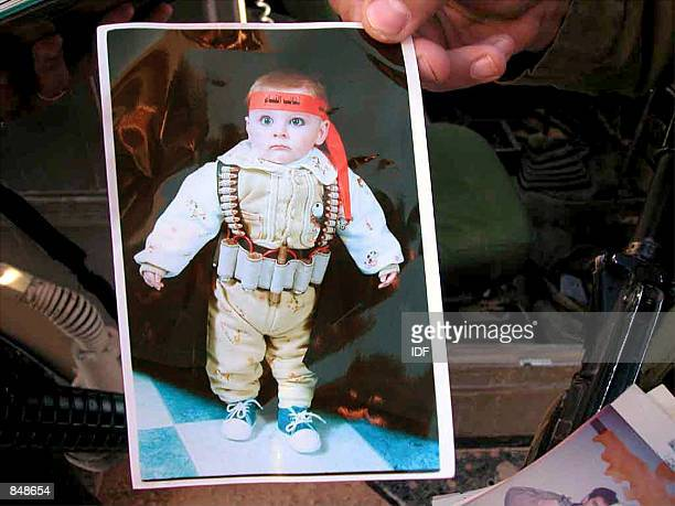 In this handout photo made available by the Israeli army June 27, 2002 an Israeli soldier holds a photograph of a Palestinian baby dressed as a...