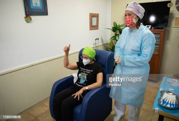 In this handout photo, Maria Carmen Cortés a nurse at the Somontano residence celebrates moments before receiving one of the first Pfizer/BioNTech...