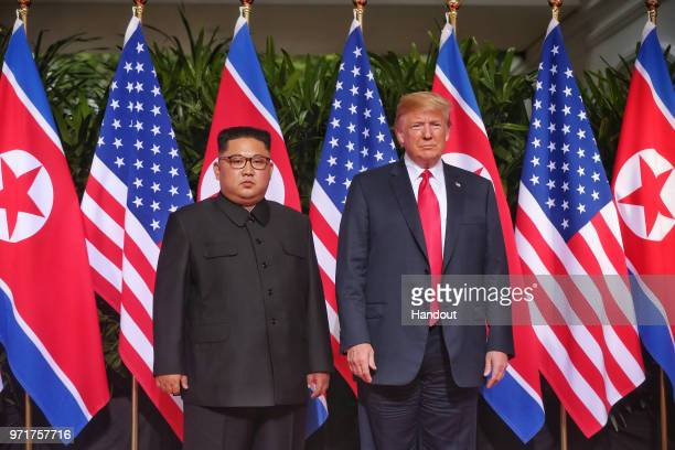In this handout photo North Korean leader Kim Jongun meets US President Donald Trump during their historic USDPRK summit at the Capella Hotel on...