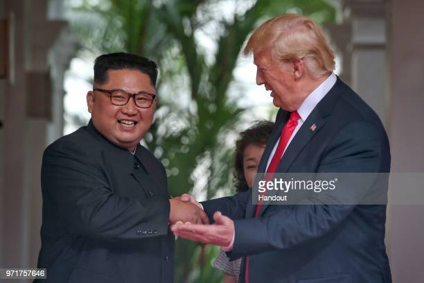 In this handout photo North Korean leader Kim Jongun shakes hands with US President Donald Trump during their historic USDPRK summit at the Capella...