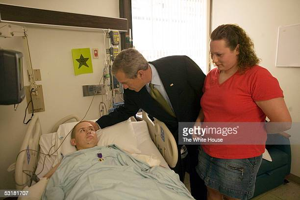 In this handout photo President George W Bush spends a moment with Pvt 2nd Class Bart Tucker of Sioux City Iowa awarded a Purple Heart for injuries...