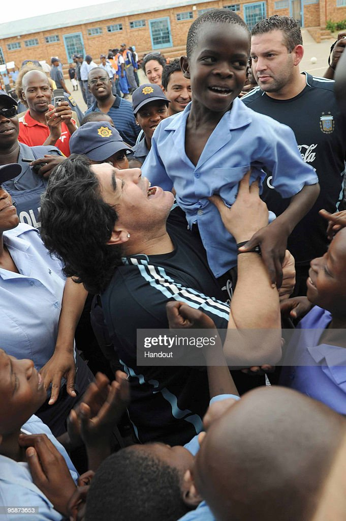 In this handout photo provided by 2010 FIFA World Cup Organising Committee South Africa, Argentina national soccer team's head coach Diego Maradona lifts up a schoolboy during his visit to Kgotlelelang School at Winterveldt on January 19, 2010, around 40km north west of Pretoria, South Africa.
