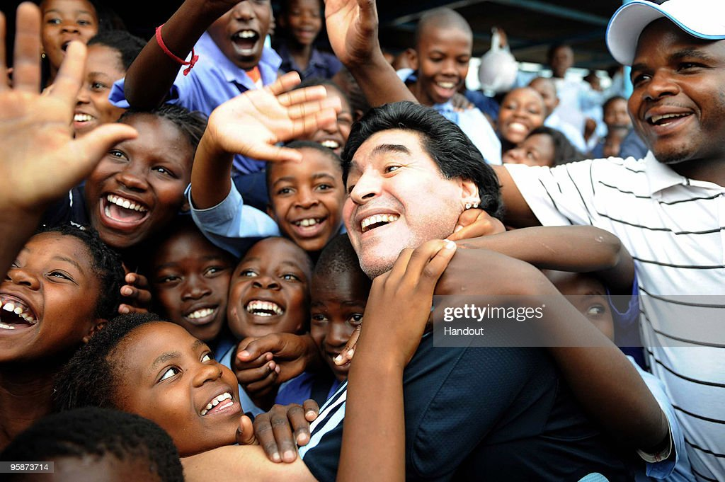 In this handout photo provided by 2010 FIFA World Cup Organising Committee South Africa, Argentina national soccer team's head coach Diego Maradona is greeted by schoolchildren during his visit to Kgotlelelang School at Winterveldt on January 19, 2010, around 40km north west of Pretoria, South Africa.