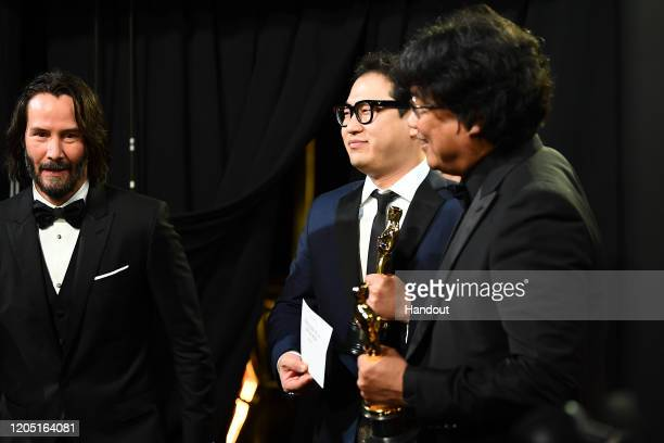 In this handout photo provided by A.M.P.A.S. Keanu Reeves and Best Original Screenplay winners Han Jin Won and Bong Joon Ho walk backstage during the...