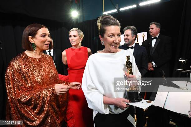 In this handout photo provided by AMPAS Maya Rudolph Kristen Wiig and Best Costume Design award winner Jacqueline Durran walk backstage during the...