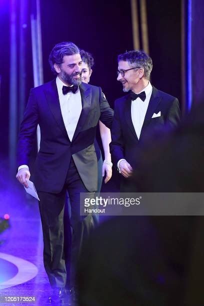 In this handout photo provided by A.M.P.A.S. Oscar Isaac and Best Sound Mixing award winner Mark Taylor walk backstage during the 92nd Annual Academy...