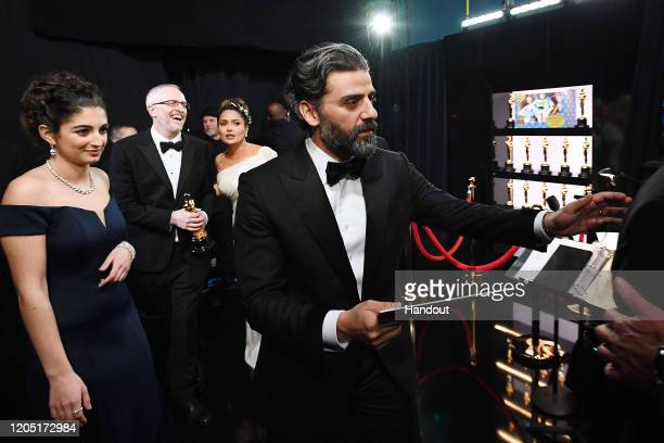 In this handout photo provided by A.M.P.A.S. Oscar Isaac walks backstage during the 92nd Annual Academy Awards at the Dolby Theatre on February 09,...
