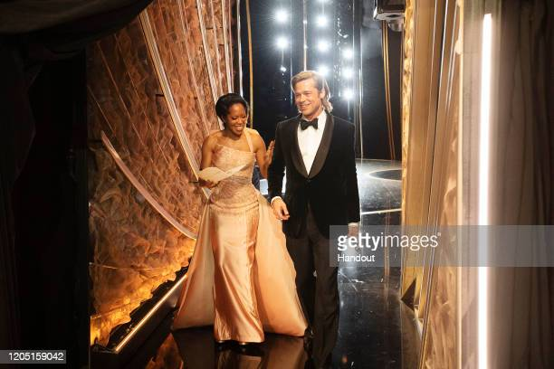 In this handout photo provided by AMPAS Regina King and Best Actor in a Supporting Role winner Brad Pitt walk backstage during the 92nd Annual...