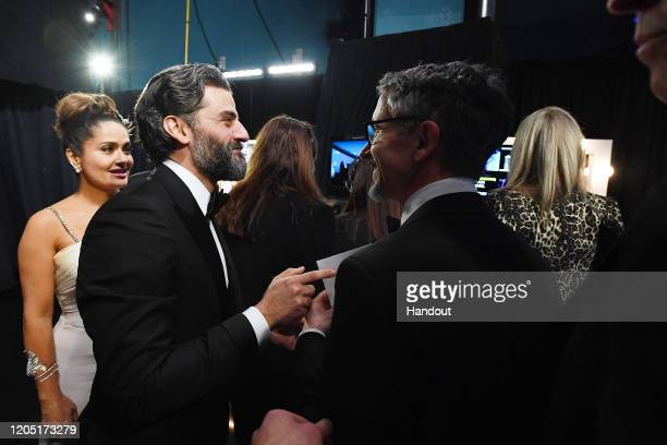 In this handout photo provided by A.M.P.A.S. Salma Hayek Pinault, Oscar Isaac, and Best Sound Mixing award winner Mark Taylor walk backstage during...