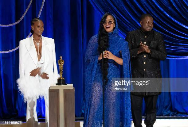 """In this handout photo provided by A.M.P.A.S., Tiara Thomas, H.E.R. And Dernst Emile II accept the Oscar for Best Original Song for """"Judas and the..."""
