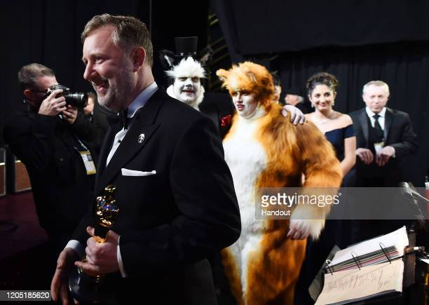 In this handout photo provided by AMPAS Visual Effects award winner Greg Butler James Corden and Rebel Wilson walk backstage during the 92nd Annual...