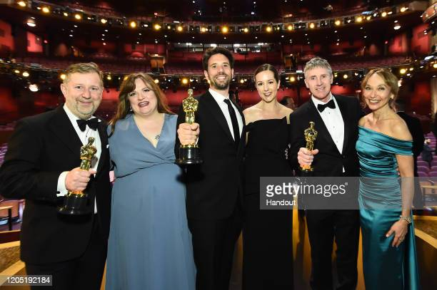 In this handout photo provided by A.M.P.A.S. Visual Effects award winners Greg Butler, Guillaume Rocheron, and Dominic Tuohy pose onstage during the...