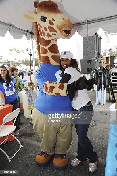 In this handout photo provided by Autism Speaks Actress Holly Robinson Peete poses together with Geoffrey the Giraffe at the Walk Now for Autism...