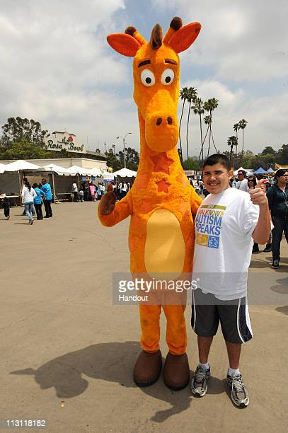 In this handout photo provided by Autism Speaks Toys R Us mascot Geoffrey the Giraffe walks with a particippant at the Walk Now for Autism Speaks on...